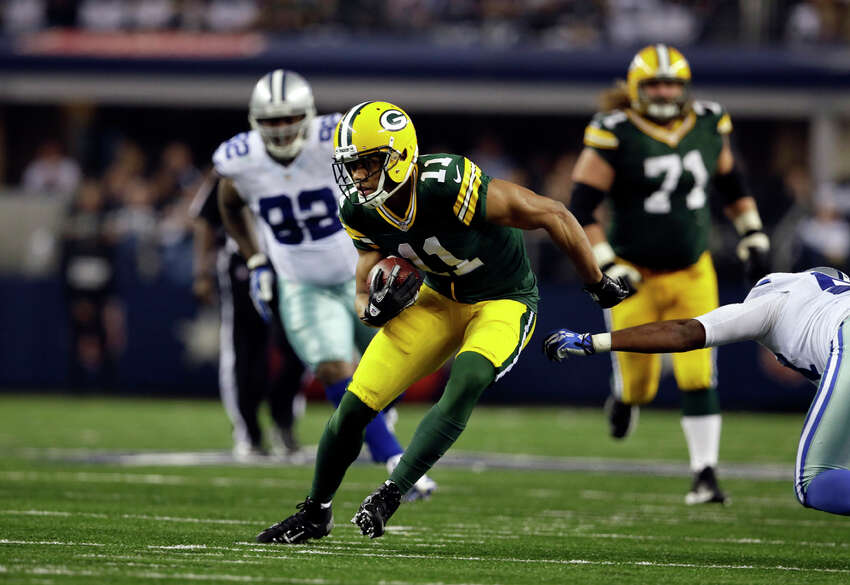 Green Bay Packers wide receiver Jarrett Boykin (11) escapes tackles after grabbing a pass during the second half of an NFL football game against the Dallas Cowboys, Sunday, Dec. 15, 2013, in Arlington, Texas. (AP Photo/Tony Gutierrez)
