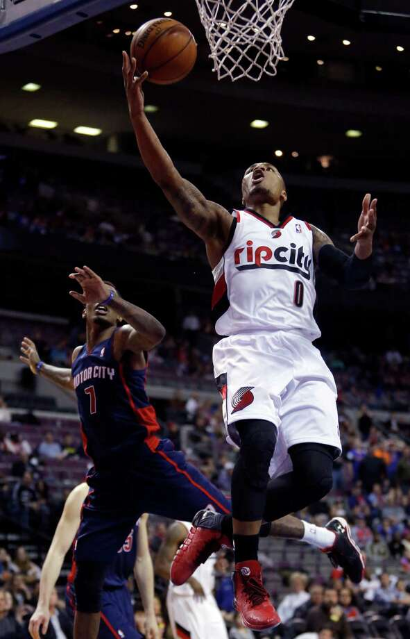 Portland Trail Blazers guard Damian Lillard (0) goes to the basket past Detroit Pistons guard Brandon Jennings (7) during overtime of an NBA basketball game Sunday, Dec. 15, 2013, in Auburn Hills, Mich. The Trail Blazers defeated the Pistons 111-109 in overtime. (AP Photo/Duane Burleson) ORG XMIT: DTP111 Photo: Duane Burleson / FR38952 AP