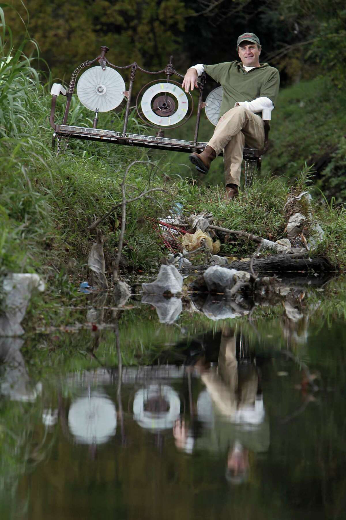 One man's trash is another man's treasure for local artist Sam Jones, who relaxes on a bench he crafted from all kinds of objects he collected along Kuhlman Gully in southeast Houston.