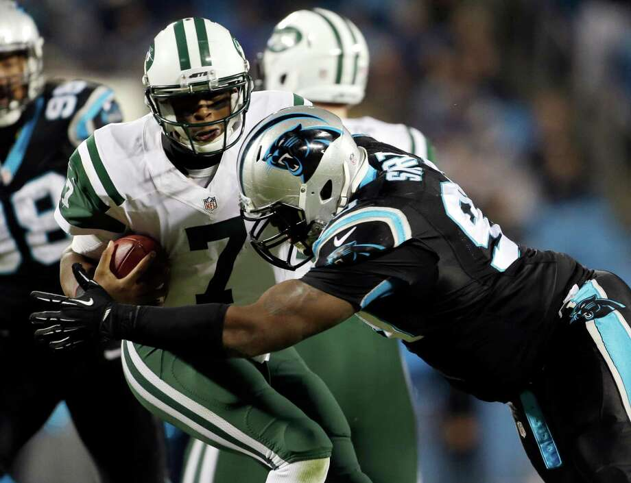 New York Jets' Geno Smith, left, is sacked by Carolina Panthers' Kawann Short, right, during the second half of an NFL football game in Charlotte, N.C., Sunday, Dec. 15, 2013. The Panthers won 30-20. (AP Photo/Bob Leverone) ORG XMIT: NCCB133 Photo: Bob Leverone / FR170480 AP