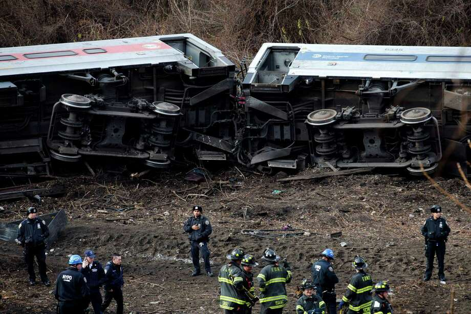 December 2013: In this Dec. 1, 2013 file photo, emergency personnel respond to the scene of a Metro-North passenger train derailment in the Bronx borough of New York. Metro-North trains are equipped with an automatic breaking system that might have prevented the crash, but the system was in place to regulate the distance between trains, not to control speeds as trains approached curves, or passed over hills and bridges. Since the crash, the speed limit was lowered on the approach to the curve, plus an alarm will sound and an automatic braking system will engage is a train approaches the bend too fast.  (AP Photo/John Minchillo, File) ORG XMIT: NYR403 Photo: John Minchillo / FR61802 AP