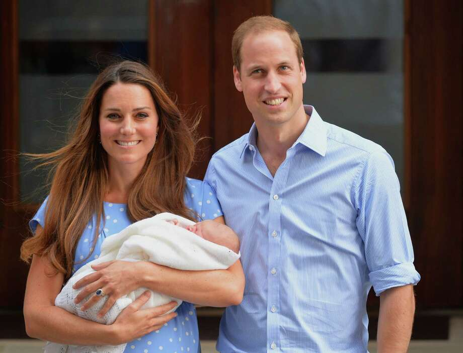 -- AFP PICTURES OF THE YEAR 2013 -- Prince William and Catherine, Duchess of Cambridge show their new-born baby boy to the world's media, standing on the steps outside the Lindo Wing of St Mary's Hospital in London on July 23, 2013. The baby was born on Monday afternoon weighing eight pounds six ounces (3.8 kilogrammes). The baby, titled His Royal Highness, Prince (name) of Cambridge, is directly in line to inherit the throne after Charles, Queen Elizabeth II's eldest son and heir, and his eldest son William.  AFP PHOTO / LEON NEALLEON NEAL/AFP/Getty Images ORG XMIT: - ORG XMIT: MER2013121317432770 Photo: LEON NEAL / AFP