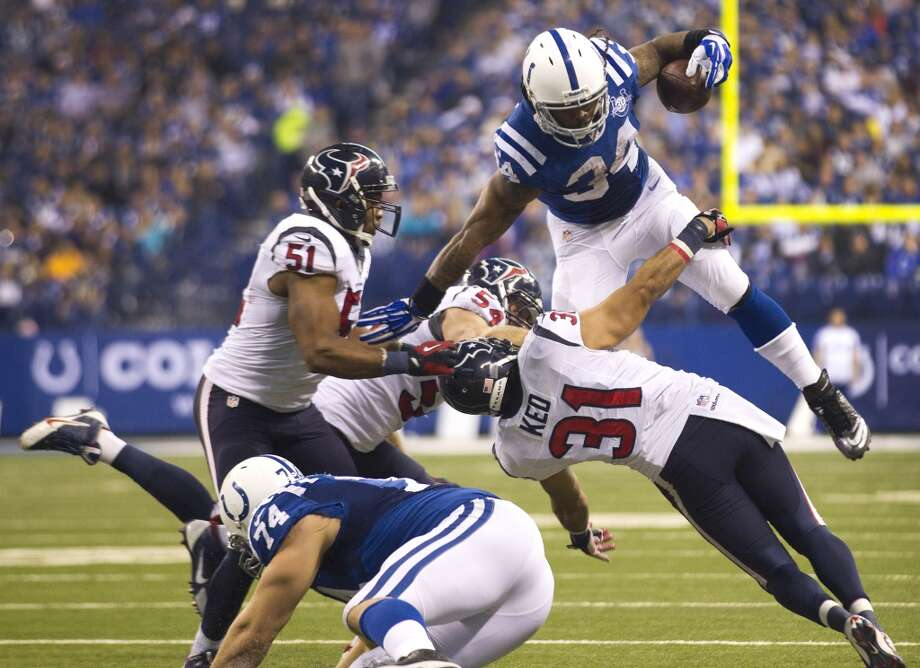 Colts running back Trent Richardson (34) leaps over Texans free safety Shiloh Keo. Photo: Brett Coomer, Houston Chronicle