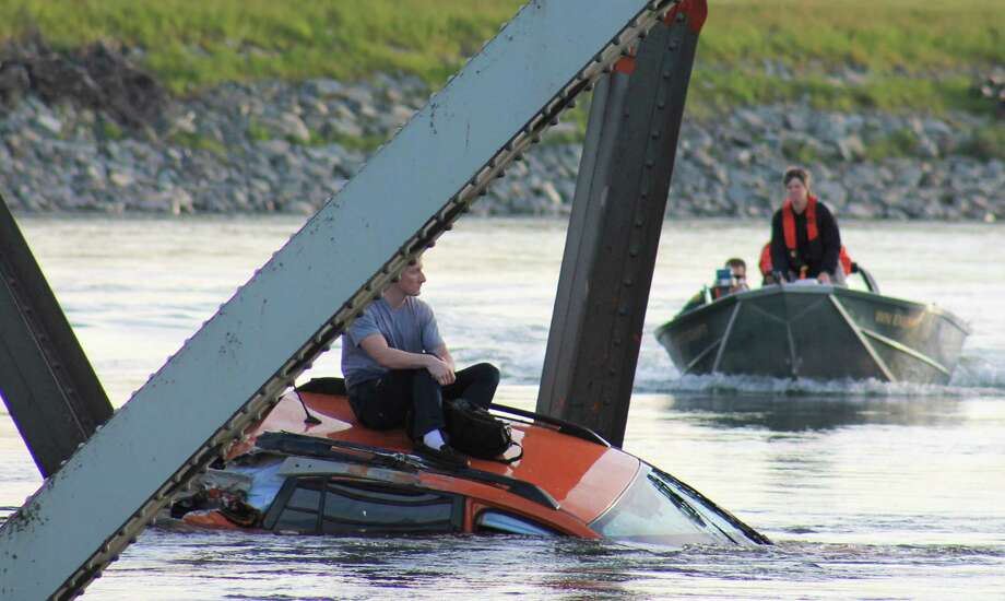 May 23, 2013— Bryce Kenning sits on the roof of his car after a section of the Interstate 5 bridge over the Skagit River collapsed between Mt. Vernon and Burlington. Two cars and one travel trailer went in the water after a truck hauling an oversized load struck part of the bridge, sending a span crashing into the river below. There were no serious injuries in the accident but the accident rerouted