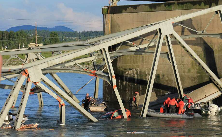 May 23, 2013 — Rescue workers attend to stranded motorists after a section of the Interstate 5 bridge over the Skagit River collapsed between Mt. Vernon and Burlington. Two cars and one travel trailer went in the water after a truck hauling an oversized load struck part of the bridge, sending a section crashing into the river below. There were no serious injuries in the accident but the accident rerouted