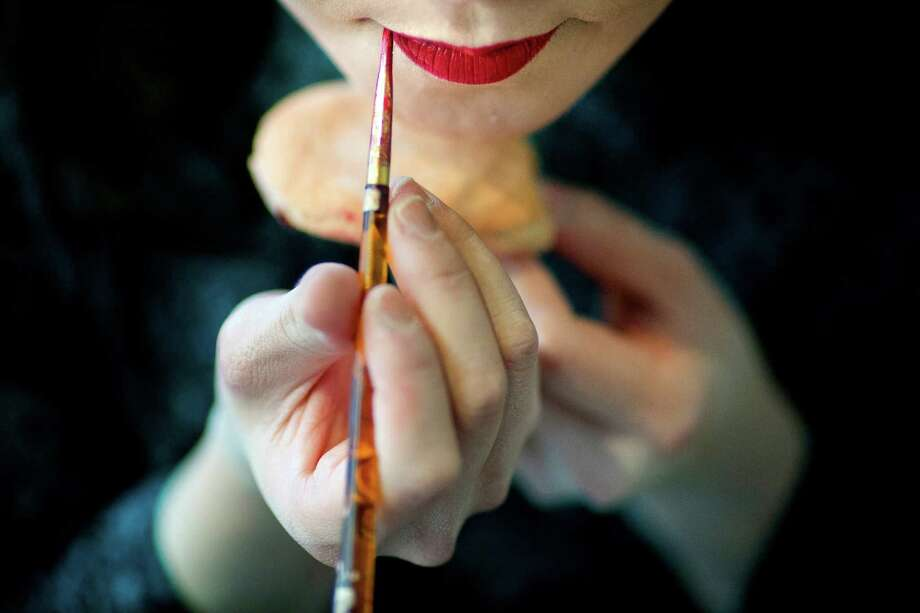 April 27, 2013 — Mawa Yoshida, of the Minori Nago Sanshin, paints her lips before her performance at the 38th annual Cherry Blossom and Japanese Cultural Festival at The Armory in Seattle. The festival boasted over 60 traditional performing arts and craft stations, drawing acts from as far away as Okinawa, Japan. Photo: JORDAN STEAD, SEATTLEPI.COM / SEATTLEPI.COM