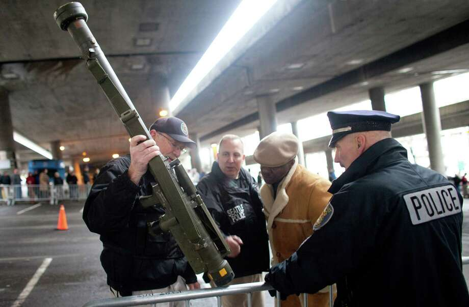 January 26, 2013 — Seattle Police Department officers examine an inert surface to air missile launcher brought to the City of Seattle's gun buy back program. The program handed out $80,000 worth of gift cards in exchange for weapons brought in by the public. The surface to air launcher was brought to the buyback and then purchased from a person in line for $100 by another citizen. Police took the already used, single use weapon until they could determine if it was safe and if the man could have it back. Photo: JOSHUA TRUJILLO, SEATTLEPI.COM / SEATTLEPI.COM