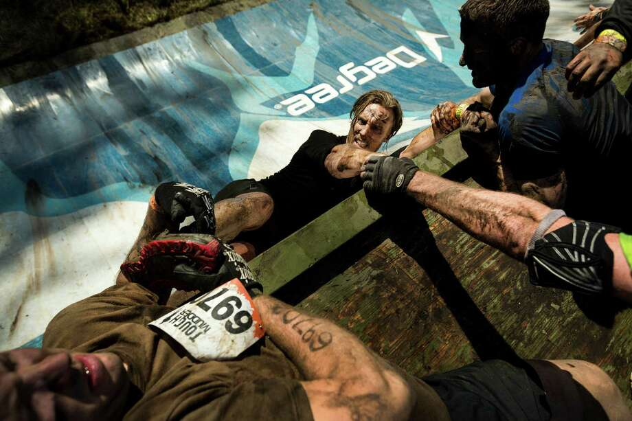 "October 5, 2013 — Teammates pull each other to the top of an ""Everest"" station wall on a Tough Mudder course in Black Diamond. Tough Mudder events involve hardcore obstacle courses, testing attendee strength, stamina and camaraderie. Photo: JORDAN STEAD, SEATTLEPI.COM / SEATTLEPI.COM"