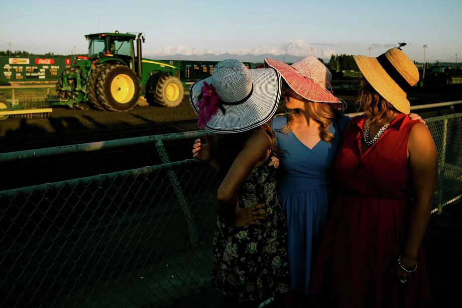 July 12, 2013 — Young women watch a tractor smooth out the dirt of the horse track at Emerald Downs in Auburn. Photo: JORDAN STEAD, SEATTLEPI.COM / SEATTLEPI.COM