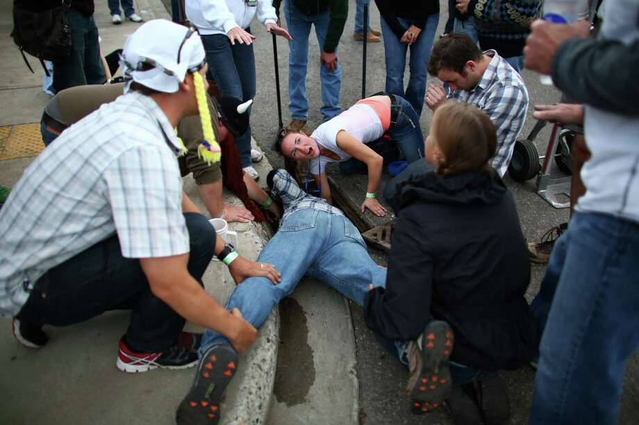 October 5, 2013 — People work to find Katy Henriksen's engagement ring after it fell off her finger and tumbled into a storm drain in the middle of Leavenworth's Oktoberfest celebration. Her fiance, Erick Mathiasen, top right, enlisted help to eventually find the ring. When passerby Jerod Henning finally came up with the ring after scooping handfuls of muck out of the drain, a crowd that had gathered erupted in cheers and celebration. Photo: JOSHUA TRUJILLO, SEATTLEPI.COM / SEATTLEPI.COM