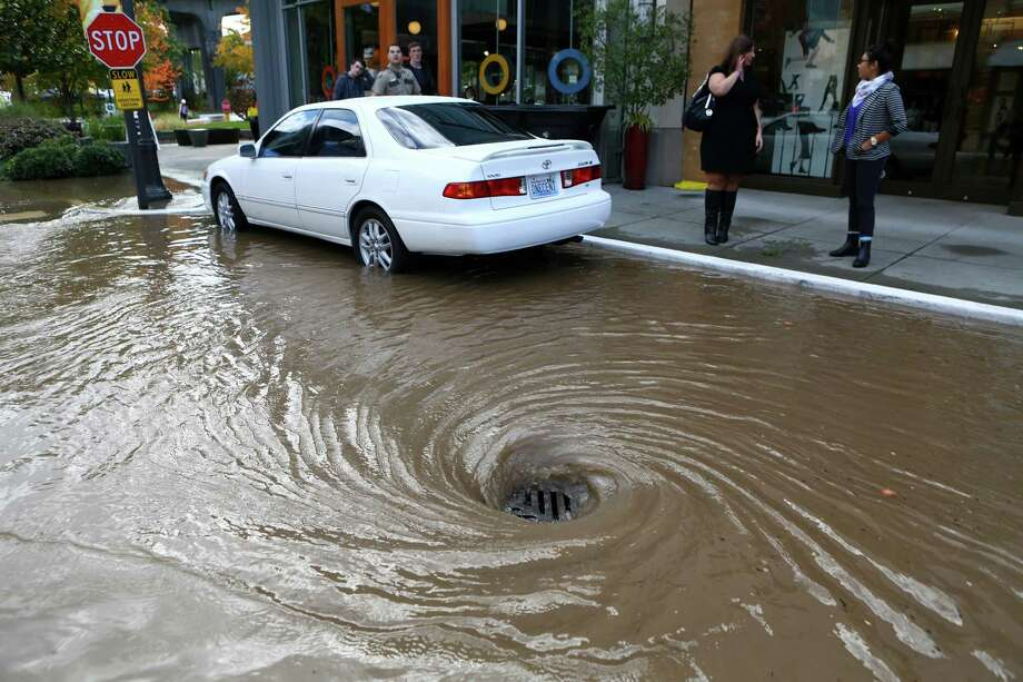October 8, 2013— Water swirls down a drain after a water main burst under the NE 45th Street Viaduct, flooding the streets of University Village. Stores and businesses in the popular shopping destination were spared from the flood of water as it flowed down drains and into parking lots. Photo: JOSHUA TRUJILLO, SEATTLEPI.COM / SEATTLEPI.COM