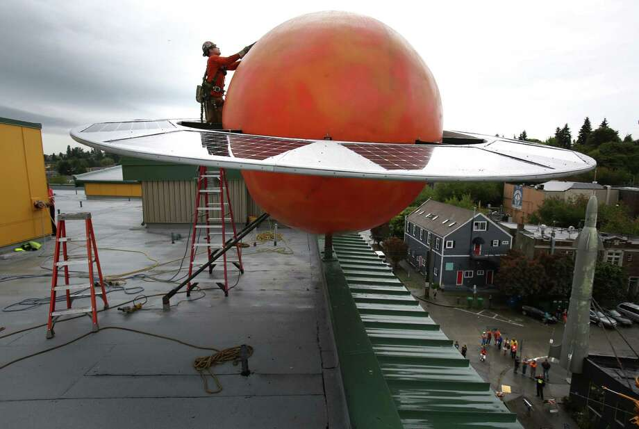 """August 29, 2013— Crane rigger Andrew Reynolds removes rigging as a 12 foot-tall fiberglass replica of the planet Saturn is installed on the roof of Fremont's Saturn Building. The large orange orb, complete with a ring of solar panels, was installed across the street from the Fremont rocket, in the """"center of the universe."""" Photo: JOSHUA TRUJILLO, SEATTLEPI.COM / SEATTLEPI.COM"""