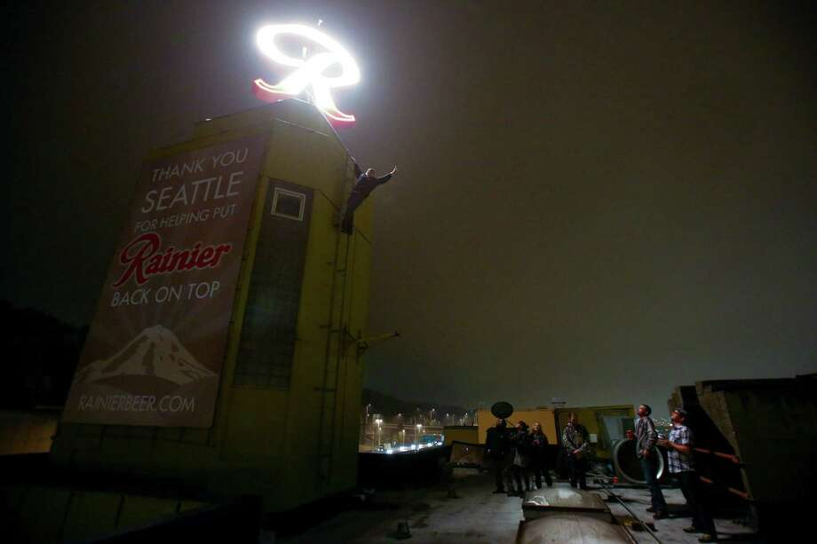 "October 25, 2013 — People gather on the roof shortly after the Rainier Beer ""R"" was hoisted to its spot at the top of the old Rainier Brewery during a community celebration. The ""R"" replaced the Tully's Coffee ""T"" which had been on the building since 2000. The ""R"" had been a Seattle icon for 50 years before the green ""T"" took its place. Photo: JOSHUA TRUJILLO, SEATTLEPI.COM / SEATTLEPI.COM"