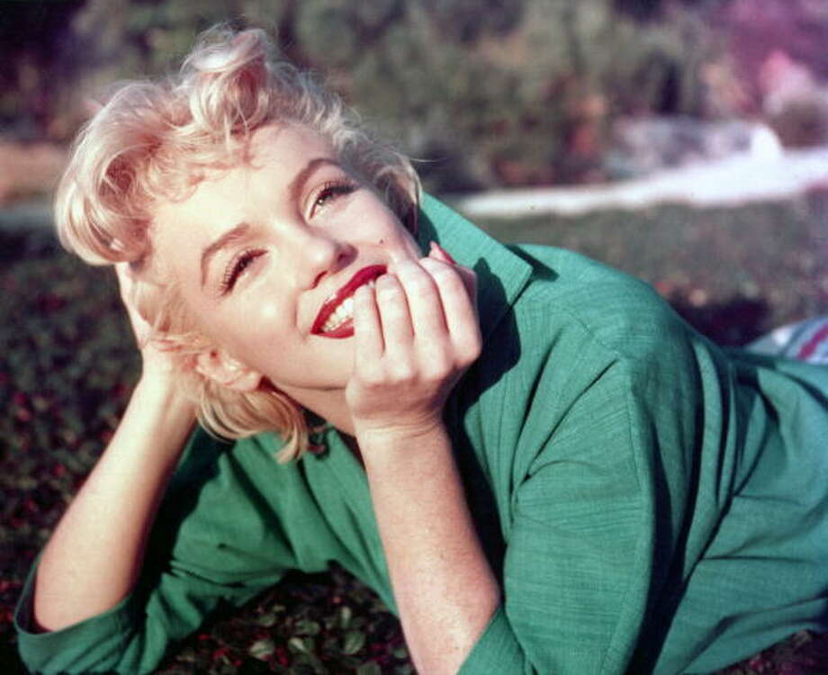 Marilyn Monroe poses for a portrait on the grass in 1954 in Palm Springs, California. Photo: Michael Ochs Archives