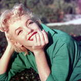 Marilyn Monroe poses for a portrait on the grass in 1954 in Palm Springs, California.