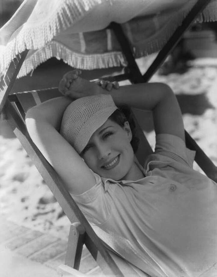 Canadian actress Norma Shearer (1902 - 1983) relaxes on a deckchair under the shade of a parasol. Photo: George Hurrell, Getty Images