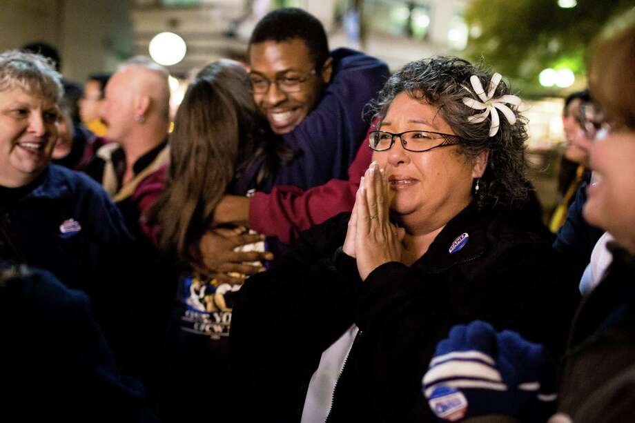 October 21, 2013 — Twenty-seven-year Safeway employee and checker Rhoda Ivie, center right, attempts to hold back tears of happiness during a celebration following the cancellation of a grocery strike by way of a tentative deal to keep grocery workers on the job. Photo: JORDAN STEAD, SEATTLEPI.COM / SEATTLEPI.COM