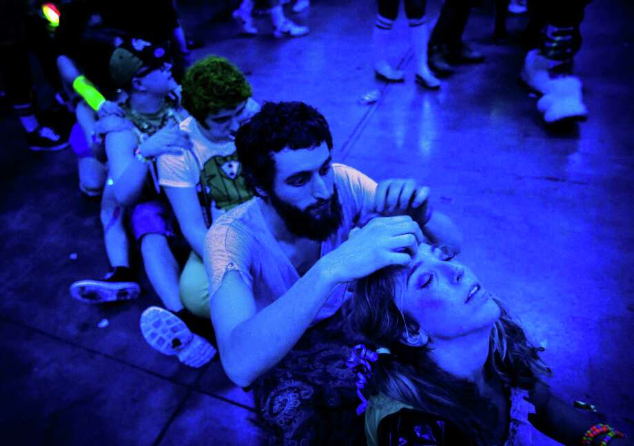 March 15, 2013 — Attendees massage each other between sets at Lucky 2013 at WaMu Theater in Seattle. Tens of thousands of glittery, green-clad people flocked to the electronic music festival to listen to nearly 30 artists spread over four stages. Photo: JORDAN STEAD, SEATTLEPI.COM / SEATTLEPI.COM