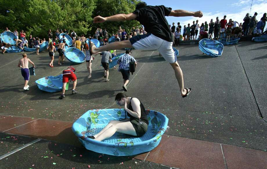 August 17, 2013— A man leaps over a person sliding into the International Fountain in a kiddie pool that was used to hold water balloons during an attempt to set a Guinness World Record for the largest water balloon fight. The group of 4,256 human water balloon cannons were unable to smash the previous record of 8,957 set in 2011 by the University of Kentucky. But they still had fun with the kiddie pools after their attempt. 300,000 water balloons were thrown during the event at Seattle Center. Photo: JOSHUA TRUJILLO, SEATTLEPI.COM / SEATTLEPI.COM