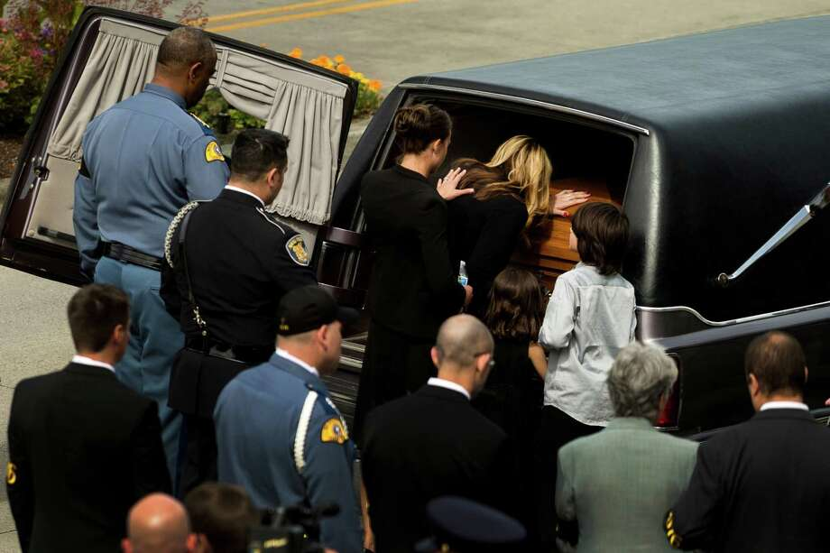 June 6, 2013 — Alissa O'Connell, center top, widow of Washington State Trooper Sean O'Connell, places her hand on the casket carrying the body of her husband following a memorial service at Comcast Arena in Everett. Following a 13-mile vehicular procession, thousands of friends, family and law enforcement attended the ceremony. O'Connell was killed in a collision with a truck. Photo: JORDAN STEAD, SEATTLEPI.COM / SEATTLEPI.COM