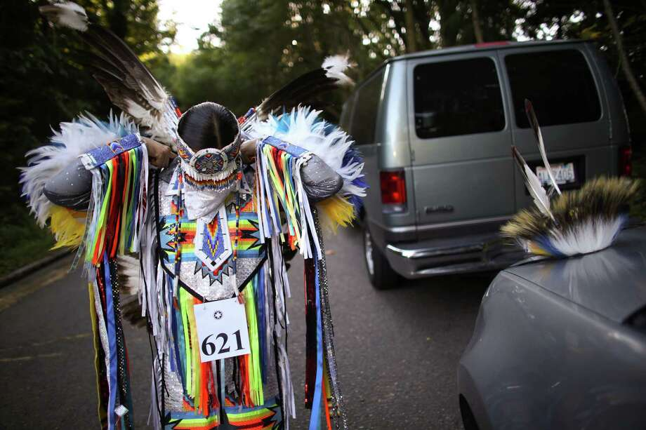 July 19, 2013 — Dennison Brown of Arizona's San Carlos Apache puts on his feathered regalia during the Seafair Indian Days Pow Wow at Daybreak Star in Discovery Park in Seattle. One year after the event was cancelled because of a lack of funding, the pow wow returned with much fanfare and a grand entry on Friday evening. The event brings Native dancers and drummers from around North America where the dancers compete in their impressive regalia during the event. The pow wow also features Native arts vendors and food booths. Photo: JOSHUA TRUJILLO, SEATTLEPI.COM / SEATTLEPI.COM