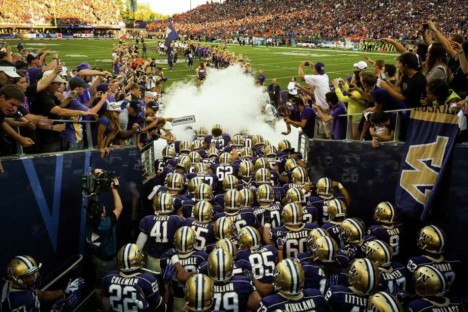 August 31, 2013— Amid smoke and cheering fans, the Washington Huskies pour out onto the turf before the opening season game against Boise State at the University of Washington's newly-renovated Husky Stadium in Seattle. Photo: JORDAN STEAD, SEATTLEPI.COM / SEATTLEPI.COM