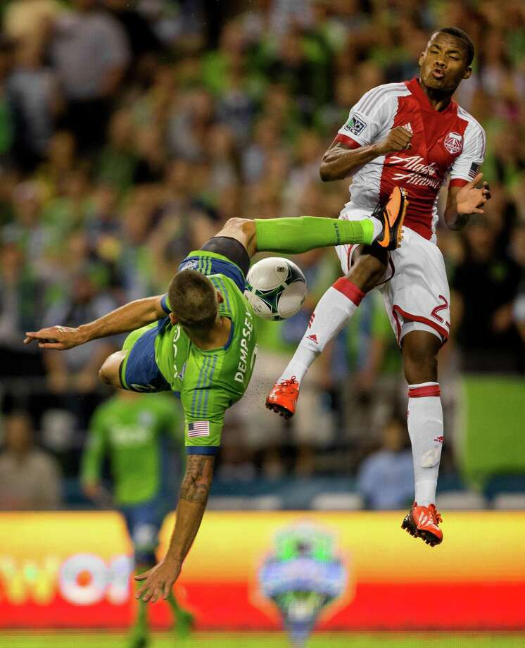 August 25, 2013 — Clint Dempsey, left, goes up for a shot against the Portland Timbers with a bicycle kick that nearly struck Alvas Powell, right, during the second half of the Cascadia Cup match at CenturyLink Field in Seattle. The Sounders beat the Timbers 1-0. The sold-out match marked Clint Dempsey's first home game as a member of the Seattle Sounders FC. Photo: JORDAN STEAD, SEATTLEPI.COM / SEATTLEPI.COM