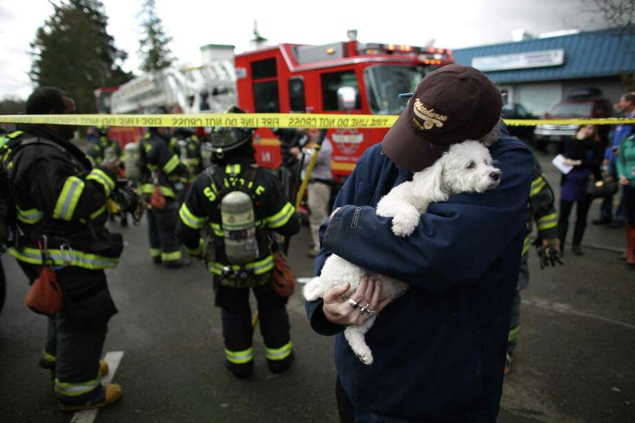 March 22, 2013— David Bailey holds onto his friend's dog Lilly after he was handed the rescued pup by a firefighter as crews battle a four-story apartment fire in Seattle's Pinehurst neighborhood. The fire damaged six units of the building and was apparently started by a burning motorcycle. Photo: JOSHUA TRUJILLO, SEATTLEPI.COM / SEATTLEPI.COM