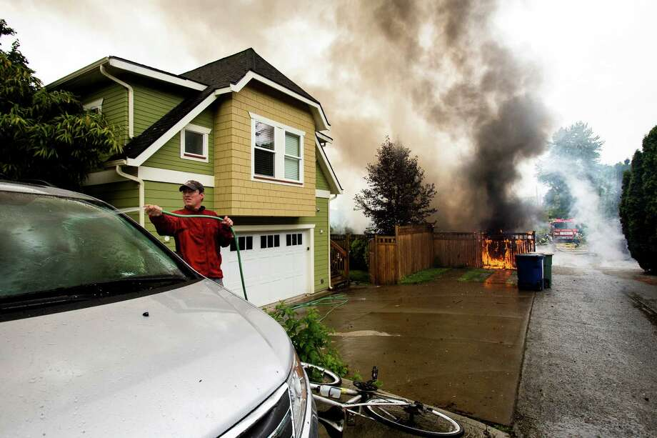 June 20, 2013 — A man waters down his car for protection as firefighters battle a garage blaze that left several other cars destroyed with no reported injuries on 22nd Avenue West in the Magnolia neighborhood of Seattle. The plume of smoke from the fire could be seen for miles. Photo: JORDAN STEAD, SEATTLEPI.COM / SEATTLEPI.COM