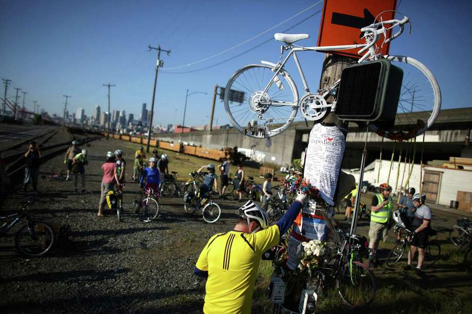 May 4, 2013 — Mourner Lars Halstron places his hand on a memorial and bows his head during a bike ride in honor of Lance David, a cyclist killed in an accident with a semi-truck on East Marginal Way South near South Hanford Street in Seattle. David, 54, was riding his bike May 1st from Federal Way on the first day of Bike to Work Month when he died. Photo: JOSHUA TRUJILLO, SEATTLEPI.COM / SEATTLEPI.COM