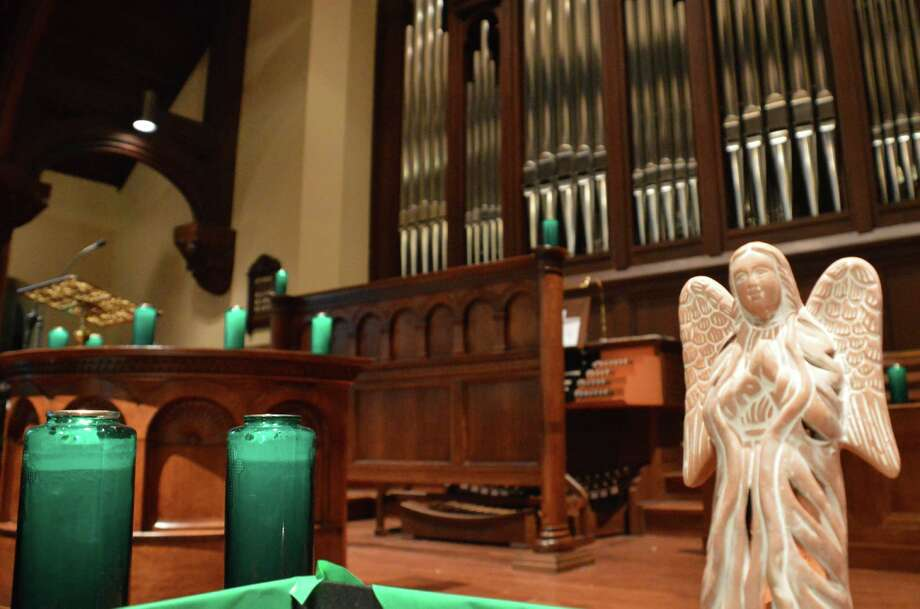 An angel and green candles -- the color of Sandy Hook Elementary School in Newtown -- set a somber tone for a vigil Sunday night for 26 victims of the school shooting. The ceremony took place in First Church Congregational. Photo: Jarret Liotta / Fairfield Citizen contributed