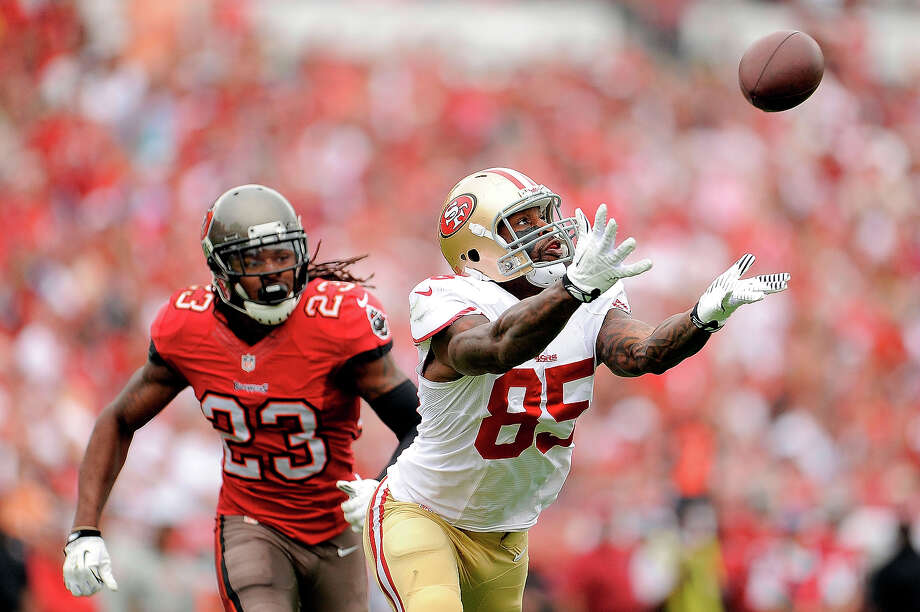 Vernon Davis #85 of the San Francisco 49ers reaches for a pass in front of Mark Barron #23 of the Tampa Bay Buccaneers during a game at Raymond James Stadium on December 15, 2013 in Tampa, Florida. Photo: Stacy Revere, Getty Images / 2013 Getty Images