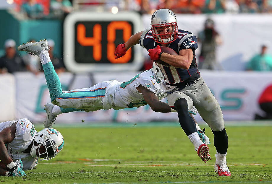 Julian Edelman #11 of the New England Patriots escapes a tackle from Nolan Carroll #28 of the Miami Dolphins during a game  at Sun Life Stadium on December 15, 2013 in Miami Gardens, Florida. Photo: Mike Ehrmann, Getty Images / 2013 Getty Images