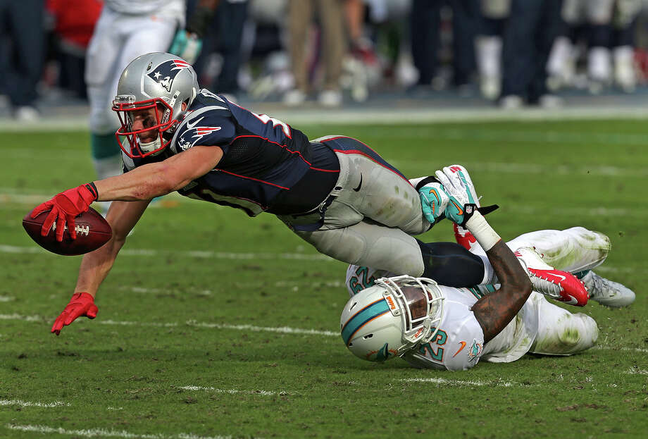New England Patriots wide receiver Julian Edelman (#11) stretches for extra yardage after a pass reception for first down in the fourth quarter. The New England Patriots take on the Miami Dolphins at SunLife Stadium. Photo: Boston Globe, Boston Globe Via Getty Images / 2013 - The Boston Globe - The Boston Globe