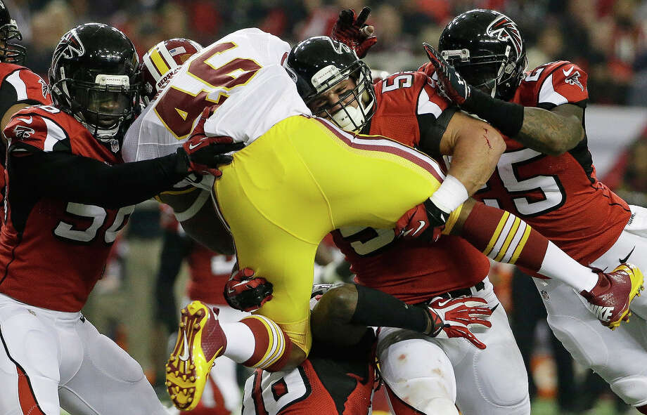 Washington Redskins running back Alfred Morris (46) is stopped by Atlanta Falcons outside linebacker Paul Worrilow (55) and other Atlanta Falcons team mates during the first half of an NFL football game, Sunday, Dec. 15, 2013, in Atlanta. Photo: David Goldman, AP / AP