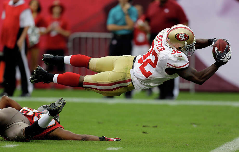 San Francisco 49ers' Kendall Hunter (32) dives into the end zone to score after picking up a fumble by Tampa Bay Buccaneers' Russell Shepard during the fourth quarter of an NFL football game Sunday, Dec. 15, 2013, in Tampa, Fla. Photo: Chris O'Meara, ASSOCIATED PRESS / AP2013