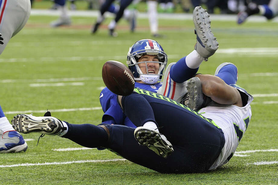 Seattle Seahawks defensive end Michael Bennett, bottom, forces a fumble off New York Giants quarterback Eli Manning  during the second half of an NFL football game on Sunday, Dec. 15, 2013, in East Rutherford, N.J. The Giants recovered their fumble on the play. Photo: Bill Kostroun, ASSOCIATED PRESS / AP2013
