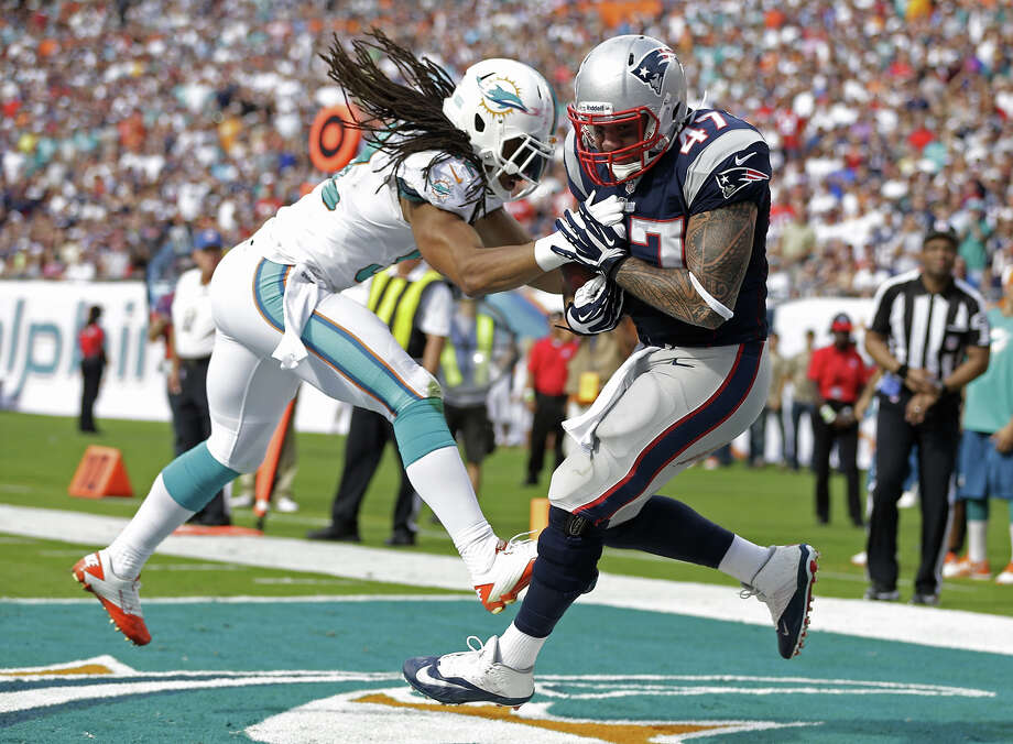 New England Patriots tight end Michael Hoomanawanui (47) grabs a touchdown pass as Miami Dolphins outside linebacker Philip Wheeler (52) defends during the first half of an NFL football game on Sunday, Dec. 15, 2013, in Miami Gardens, Fla. Photo: Lynne Sladky, ASSOCIATED PRESS / AP2013