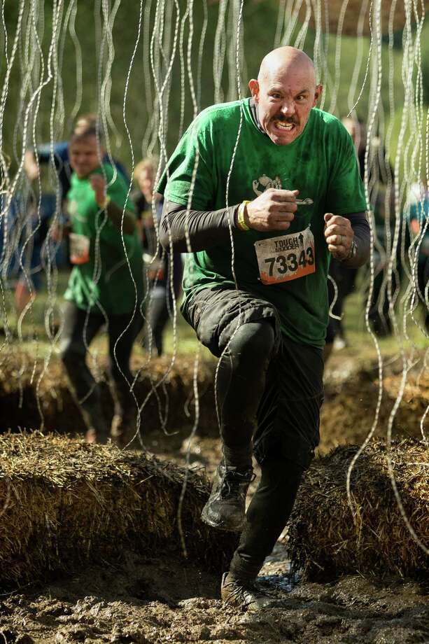 """October 5, 2013— A participant sprints through an """"Electroshock Therapy"""" station that delivers a jolt of up to 10,000 volts if touched near the finish line of the Tough Mudder course in Black Diamond. Tough Mudder events involve hardcore obstacle courses, testing strength, stamina and camaraderie. Photo: JORDAN STEAD, SEATTLEPI.COM / SEATTLEPI.COM"""