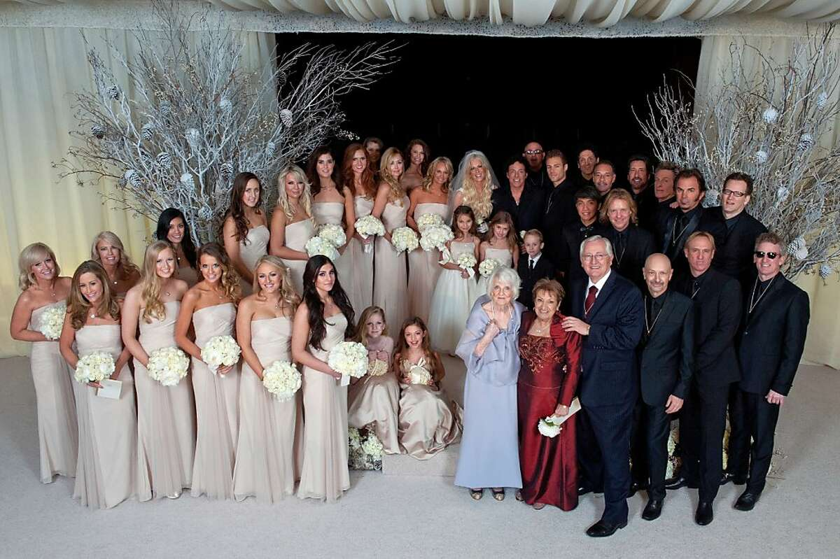SAN FRANCISCO, CA - DECEMBER 15: (EXCLUSIVE ACCESS, SPECIAL RATES APPLY) Neal Schon and Michaele Schon pose with their bridal party at their wedding at the Palace of Fine Arts on December 15, 2013 in San Francisco, California. (Photo by Robert Knight/MNS/WireImage for Schon Productions)