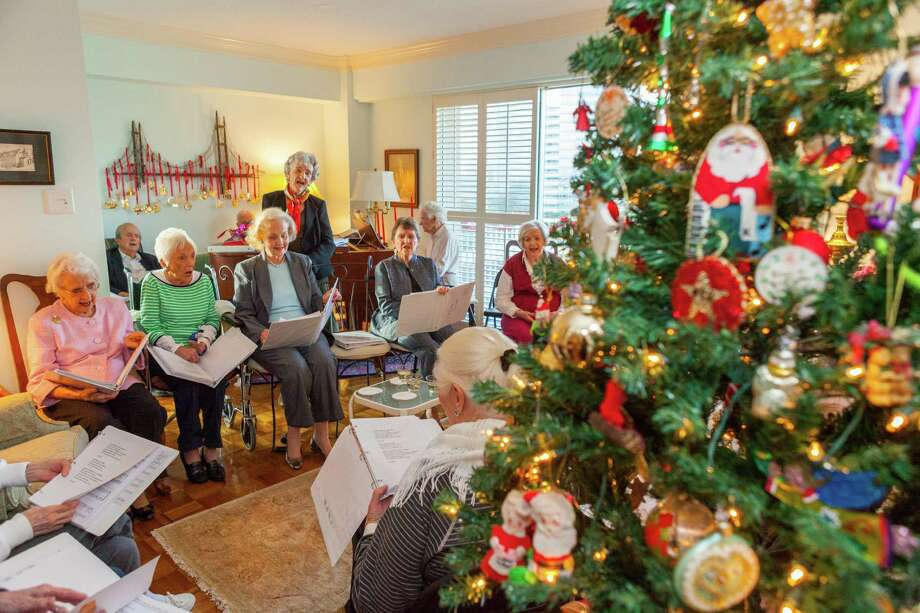The 801 Singers, residents of The Hallmark, gather weekly for a sing-along at the apartment of Ruth Giampietro, standing.