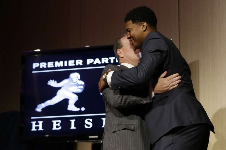 Florida State quarterback Jameis Winston, right, hugs his coach Jimbo Fisher after it was announced he won the Heisman Trophy. The following are some of the best hugs captured this year. (AP Photo/Julio Cortez) Photo: Julio Cortez, Associated Press