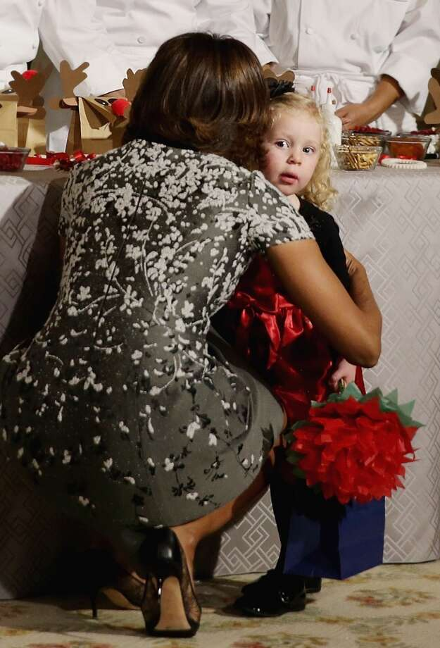 WASHINGTON, DC - DECEMBER 04:  U.S. first lady Michelle Obama hugs Ashtyn Gardner of Mobile, Alabama, at the State Dining Room of the White House during an event to preview the 2013 holiday decorations December 4, 2013 in Washington, DC. The first lady hosted military families for the first viewing of the decorations and demonstrating holiday crafts and treats to military children.  (Photo by Alex Wong/Getty Images) Photo: Alex Wong, Getty Images