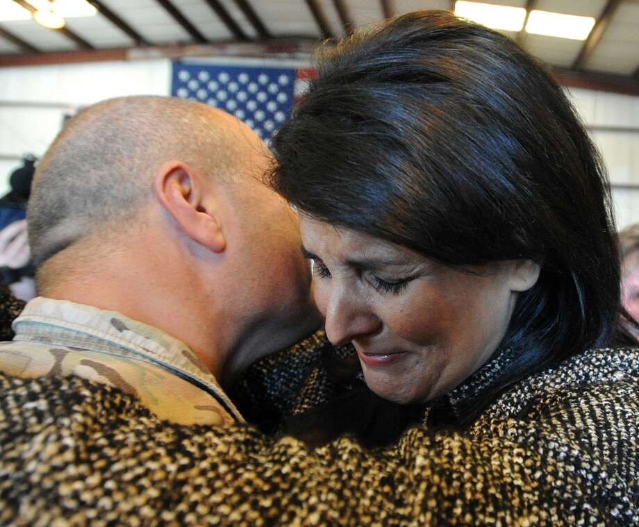 South Carolina Gov. Nikki Haley, right, hugs her husband, Capt. Michael Haley, during the South Carolina Army National Guard 3/49 Agribusiness Development Team homecoming ceremony on Thursday, Dec. 12, 2013, in West Columbia, S.C. Haley's unit, comprised of about 48 soldiers, left in January for a month of training in Indiana before being sent to train Afghan farmers in and around Helmand Province. (AP Photo/Rainier Ehrhardt) Photo: Rainier Ehrhardt, Associated Press