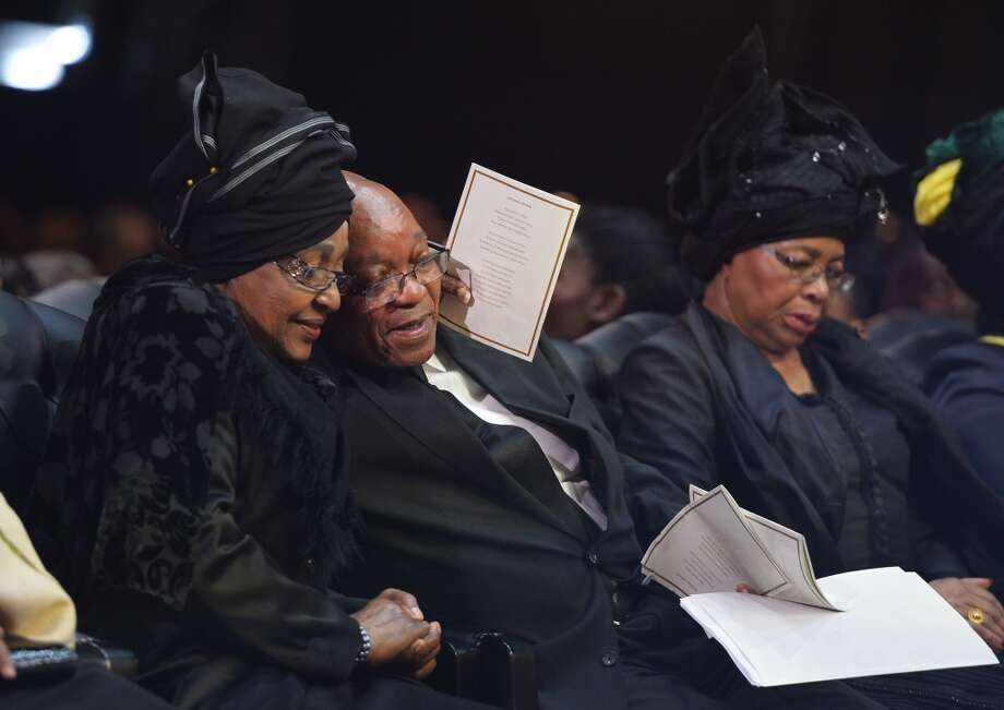Winnie Madikizela-Mandela, Nelson Mandela's former wife, hugs South African President Jacob Zuma following his speech during the funeral service for former South African President Nelson Mandela in Qunu, South Africa, Sunday, Dec. 15, 2013.  Right is Nelson Mandela's widow Graca Machel. (AP Photo/Odd Andersen, Pool) Photo: Odd Andersen, Associated Press
