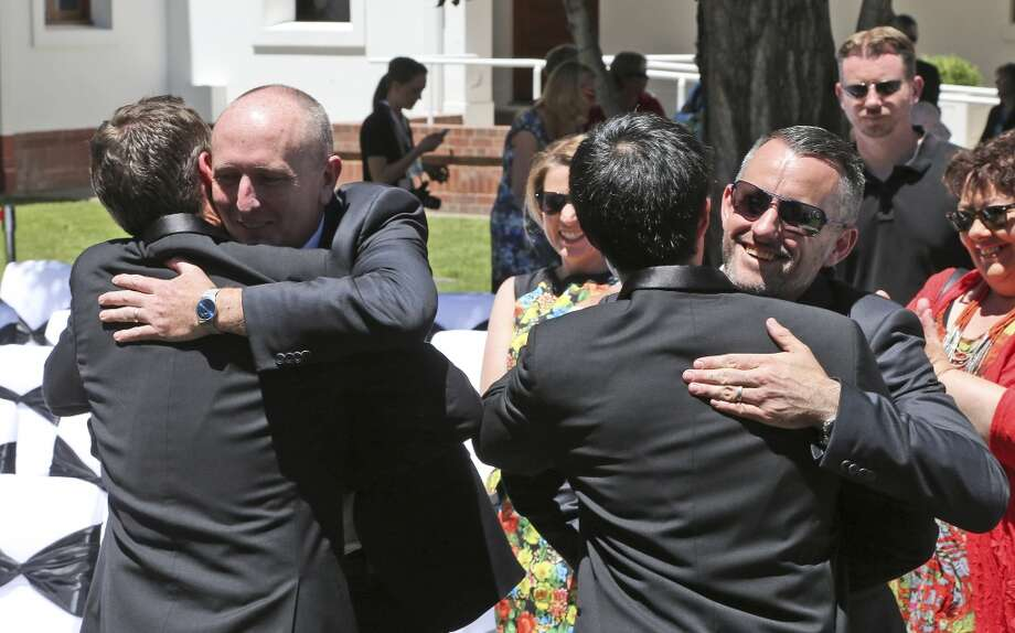 Gay couple Stephen Dawson, second from left, and Dennis Littelow, right, hug their partners Ivan Hinton, left, and Chris Teoh after they took their wedding vows during a ceremony at Old Parliament House in Canberra, Australia, Saturday, Dec. 7, 2013. Dozens of same-sex couples from all around the country are taking advantage of the Australia Capital Territory's new law allowing same-sex marriages. But the unions may be short lived if  the High Court on Dec. 12, 2013 rules in favor of a Commonwealth challenge to overrule the states law. (AP Photo/Rob Griffith) Photo: Rob Griffith, Associated Press