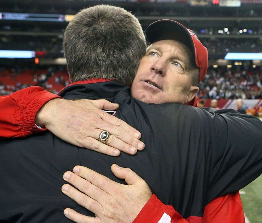 Marion County coach Mike Swaney hugs Rick McCorkle as he celebrates his teams 12-3 victory over Charlton County in the GHSA Class A-Public Football Championship game at the Georgia Dome in Atlanta on Saturday, Dec. 14, 2013. (AP Photo/Atlanta Journal-Constitution, Phil Skinner)  MARIETTA DAILY OUT; GWINNETT DAILY POST OUT; LOCAL TV OUT; WXIA-TV OUT; WGCL-TV OUT Photo: Phil Skinner, Associated Press