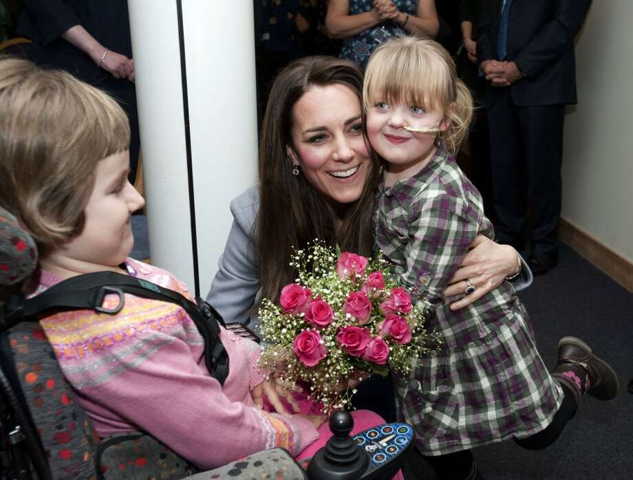 Britain's Catherine, the Duchess Of Cambridge, hugs Demi-Leigh Armstrong (R), aged 5, during a visit to the Shooting Star House Children's Hospice in Hampton, Middlesex, on December 6, 2013. AFP PHOTO/POOL/BRADLEY PAGEBRADLEY PAGE/AFP/Getty Images Photo: BRADLEY PAGE, AFP/Getty Images