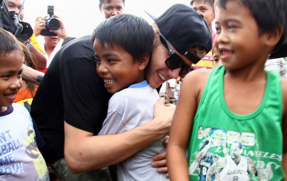 Canadian pop megastar Justin Bieber (C, black shirt) hugs a young survivor of Super Typhoon Haiyan in Palo, Leyte province on December 10, 2013. Bieber sang to and played basketball with young survivors of the Philippines' deadliest typhoon on December 10 after he flew into the disaster zone to boost an international relief effort. TOPSHOTS     AFP PHOTOSTR/AFP/Getty Images Photo: STR, AFP/Getty Images