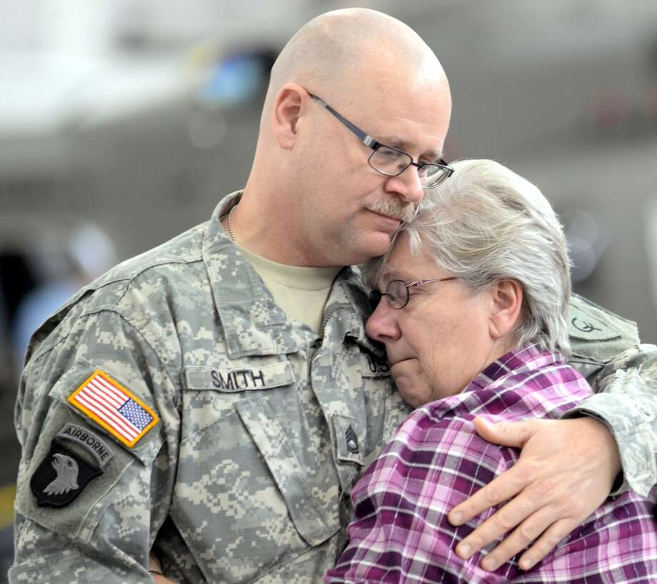 Michigan National Guard member Jeff Smith of Charlotte gets a warm hug from his mother Jan Smith of Eaton Rapids as Family and friends said goodbye to the Michigan National Guard soldiers from the Headquarters, D and E Companies, 2nd Battalion, and the 238th General Support Aviation Battalion Monday, Dec. 2, 2013 at the Grand Ledge Army Aviation Support Facility. (AP Photo/Lansing State Journal, Greg DeRuiter) Photo: Greg DeRuiter, Associated Press